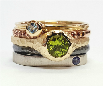 Stacking rings with Peridot, orange diamonds, sapphire, Aquamarine, and different colors of gold and sterling silver