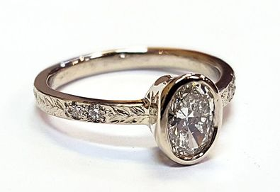 Engagement Ring With A Bezel Set Oval Diamond And Accented Hand Engraved Band